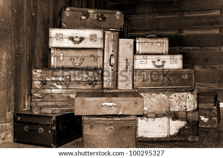 Old antique suitcases stacked up high in a station in sepia.