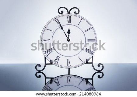 Old antique wall clock isolated on reflective floor, five minutes to twelve o\'clock
