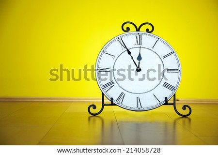 Old antique wall clock isolated on wooden floor and yellow wall background, five minutes to twelve o\'clock