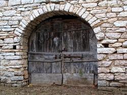 Old antique wooden door or gate. The door in the stone wall cracked.