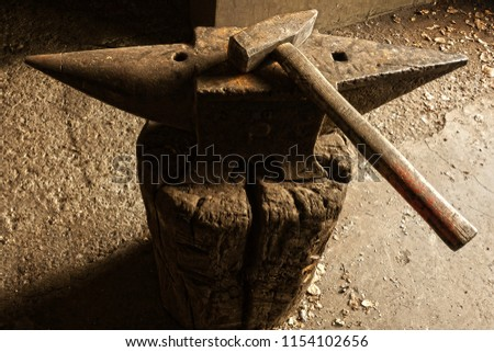 old anvil with hammer on wooden stump