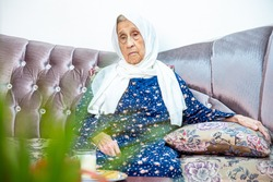 Old arabic muslim lady setting on couch feeling sad  and lonley