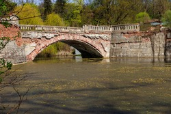 Old arched brick bridge across a pond in Sharovka Palace park in in Kharkov region, Ukraine