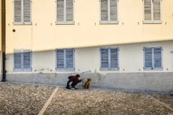 old architecture of montevecchia, woman photographing her dog, retriever for a walk, photography position, shadows on the wall of old house, new normal