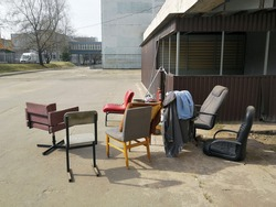 Old armchairs and chairs of various configurations and colors stand outside on a sunny day. Furniture that has fallen into disrepair is old junk.