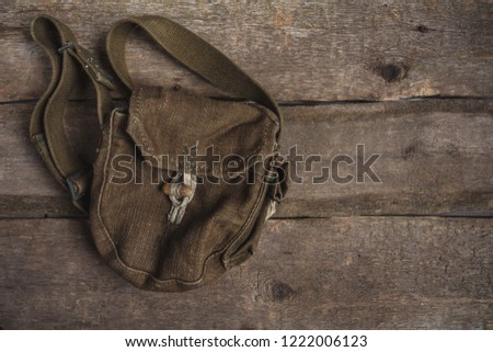 Stock Photo Old army bag, military uniform on a wooden background with copy space, flat lay top view