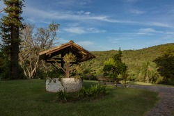 Old artesian water well transformed into a garden planter. Natural landscape. Farm field, cut grass, trees and in the background, Pedra Grande mountain and blue sky.