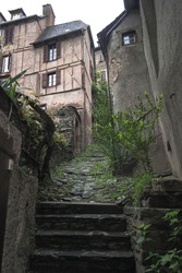 Old ascending cobbled streets in the village of Conques, Occitanie France