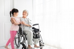 old asian female hug asian children, they feeling happy and smile, old asian people sitting on wheelchair, elderly healthcare promotion, happiness family activity