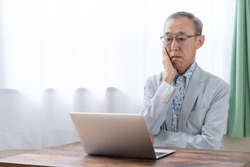 old asian man using laptop in living room