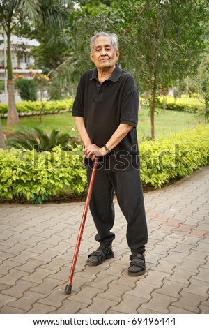 Old Asian man with walking stick - stock photo