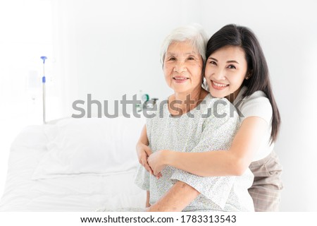 old asian patient sick and admit in hospital, young asian female visiting old female, she hug old female, they feeling happy and smile, elderly healthcare