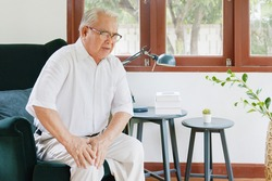 Old Asian senior man feel pain, ache, hurt at knee while standing and sitting at home, osteoarthritis concept