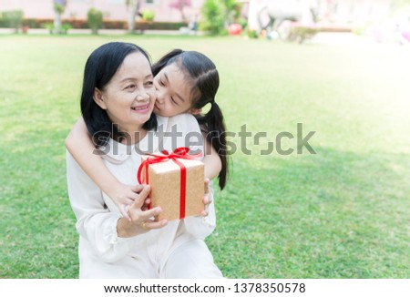 old asian woman and asian children holding gift box on nature background, they feeling happy in family time, asian children kiss her grandmother, congratulation gift, mother's day #1378350578