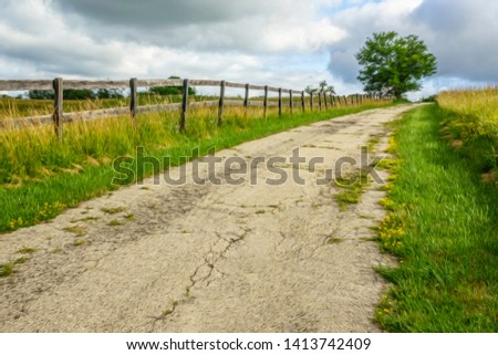 Old asphalt lane on grassy hillside with long, weathered equine fence on a cloudy day in summer, northern Illinois, USA, with digital oil-painting effect, for rural, suburban, and vintage themes