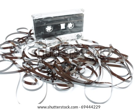 Old audio cassette tape pulled out and tangled on white background