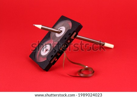 Old audio cassette with a pencil in the hole on a red background. Old rewind cassette tape with tape by pencil Сток-фото ©