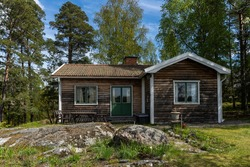 Old authentic cabin house in the woods. Dacha guest house. Nobody there. Old wooden building among forest trees for tourists relax. Roof tiles. Outdoors wooden table and chairs on the yard. Cozy place
