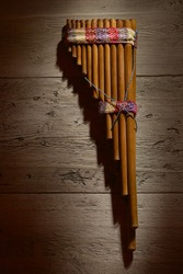 Old authentic panflute hanging on wood wall background