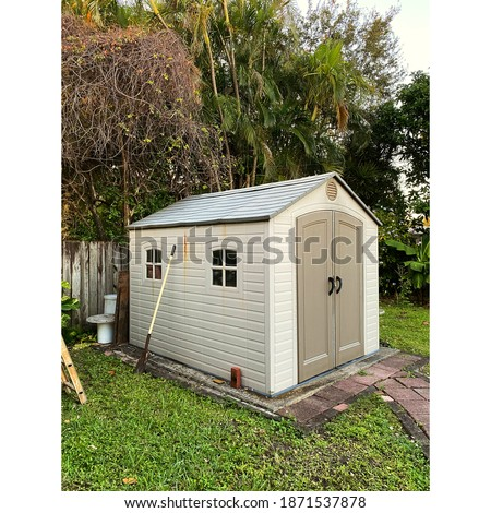 Old backyard tool shed with shovel on the outside of a yard. Many trees are surrounding the shed. Foto stock ©