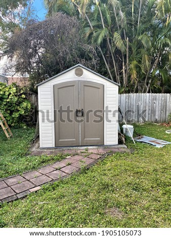 Old backyard tool shed with shovel on the outside of a yard. Many trees are surrounding the shed.