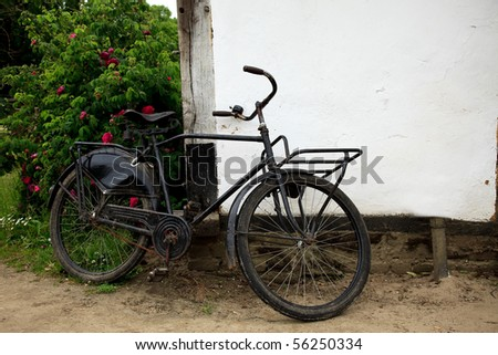 Old baker delivery bicycle parked against old house wall.  Rural live, scene
