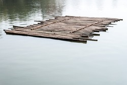 Old bamboo raft is floating on the lake in the morning.
