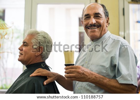 Old barber holding brush for talco and smiling to camera in old fashion barber shop