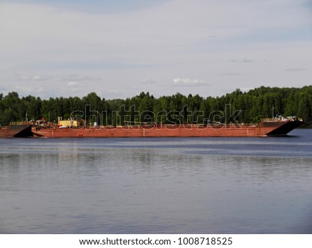 Old barge on river. Barge sailing on the river Dnieper. Barge with cargo is floating on river in summer day. Barge going up river against green forest.