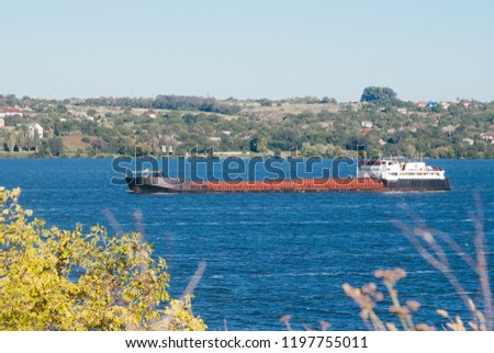 Old barge on the river. Barge floats on the Dnieper river. Barge with cargo floating on the river on a summer day