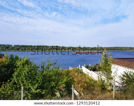 Old barge on the river. Barge floats on the Dnieper river. Barge with cargo floating on the river on a summer day.
