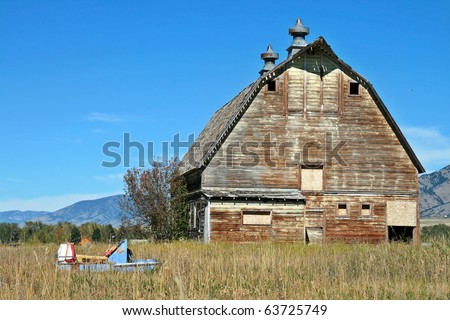 Old Barn against a blue sky with a broken snowmobile in a field