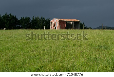 Old barn in sunlight with approaching storm in the background