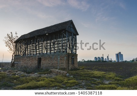 Old barn in the opposition of the new shinny silos at sunrise #1405387118