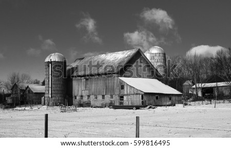 Old barn in Upstate New York with snow covered field and fence. This photo is in black and white.