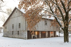 Old barn with lights on in the snow