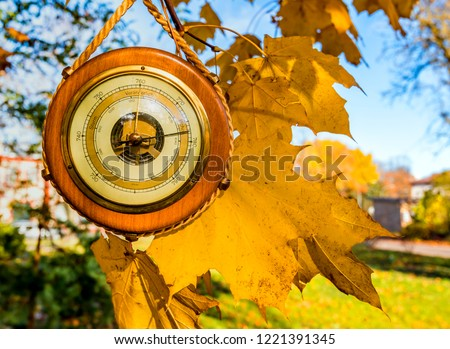 Old barometer, focus on autumnal maple leaves and instrument.   Concept of forecasting. Translations from German to English are: sturm is storm; veranderlich is changeable; schone is enjoyable   #1221391345