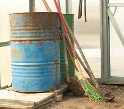 old barrels and broom stand in the greenhouse