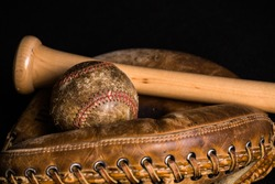 Old baseball, stained and wonrn out, and old style catchers mitt joined by a brand new baseball bat.