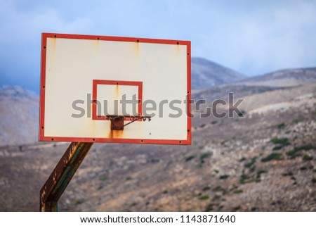 Old basketball board with basket hoop against mountains hills landscape and sky. Sport, recreation. #1143871640