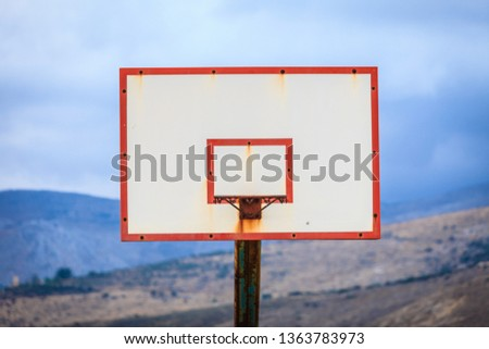 Old basketball board with basket hoop against mountains hills landscape and sky. Sport, recreation. #1363783973