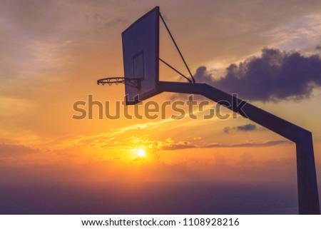 Old basketball board with basket hoop against sunset sky. Sport, recreation. #1108928216