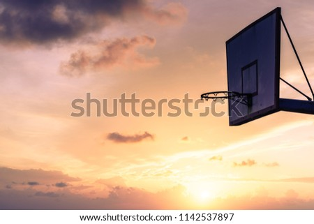 Old basketball board with basket hoop against sunset sky. Sport, recreation. #1142537897