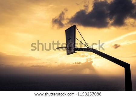 Old basketball board with basket hoop against sunset sky. Sport, recreation. #1153257088