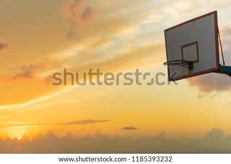 Old basketball board with basket hoop against sunset sky. Sport, recreation. #1185393232