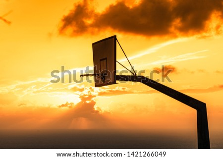 Old basketball board with basket hoop against sunset sky. Sport, recreation. #1421266049