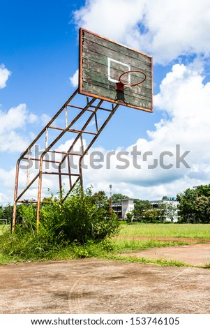 Old basketball hoop and wooden board on blue sky background