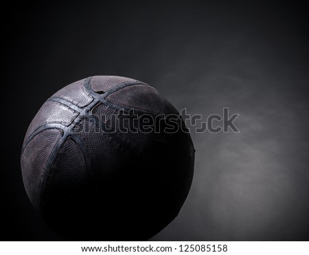 old basketball on a black background - stock photo