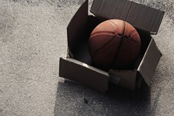 Old basketball. Unused ball in the paper box.