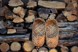 Old Bast shoes - traditional Russian footwear. vintage Russian national shoes - Lapti, bast sandals. Shoes made from bark of tree. rural bast shoes on wooden backdrop, pile of firewood. copy space